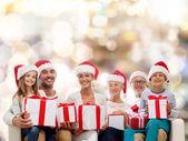 Gelukkige familie in santa helper hoeden met geschenkdozen — Stockfoto