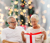 happy senior couple with gift box at home — Stok fotoğraf