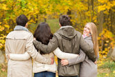 Group of smiling men and women in autumn park — Stock Photo
