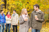 Group of smiling friend with coffee cups in park — Stock Photo