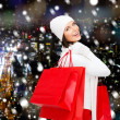 Smiling young woman with red shopping bags — Stock Photo #55983217
