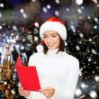 Smiling woman in santa hat with greeting card — Stock Photo #55983515