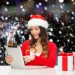 Smiling woman in santa hat with gift and tablet pc — Stock Photo #55984585