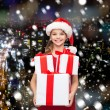 Smiling little girl in santa helper hat with gifts — Stock Photo #55986385