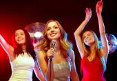 Three smiling women dancing and singing karaoke — Stock Photo