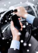 Close up of man using smartphone while driving car — Stockfoto