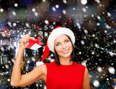 Smiling woman in santa hat with jingle bells — Stock Photo