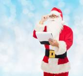 Man in costume of santa claus with notepad — Stock Photo