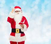 Man in costume of santa claus with notepad — Stockfoto