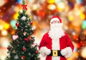Man in costume of santa claus with christmas tree — Foto Stock