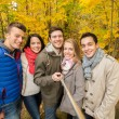Smiling friends with smartphone in city park — Stock Photo #55990785