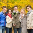 Smiling friends with smartphone in city park — Stock Photo #55990849