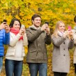 Smiling friends with smartphones in city park — Stock Photo #55990911
