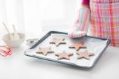 Close up of woman with cookies on oven tray — Stock Photo