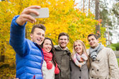 Smiling friends with smartphone in city park — Stock Photo
