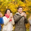 Smiling friends with smartphones in city park — Stock Photo #56031107