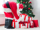 Man in costume of santa claus with presents — ストック写真