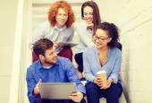 Team with laptop and tablet pc on staircase — Stock Photo