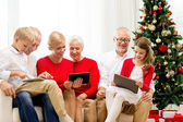Smiling family with tablet pc computers at home — Stock Photo