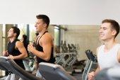 Smiling men exercising on treadmill in gym — Stock Photo