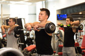 Group of men with barbells in gym — Stock Photo