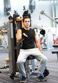 Man exercising on gym machine — Stock Photo