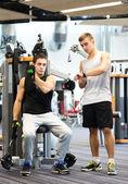 Men exercising on gym machine — Stock Photo