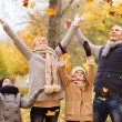 Happy family playing with autumn leaves in park — Stock Photo #56071607