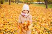 Smiling little girl with autumn leaves in park — Stock Photo
