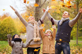Happy family playing with autumn leaves in park — Stockfoto