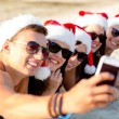Group of friends in santa hats with smartphone — Stock Photo #56118809