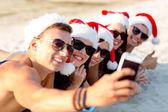 群在圣诞老人的帽子,与智能手机的朋友 — 图库照片
