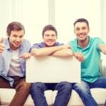 Erkek arkadaşlar beyaz boş tahta tutan gülümseyerek — Stok fotoğraf #56171199