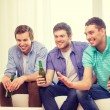 Happy male friends with beer watching tv at home — Stock Photo #56172317