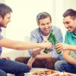 Smiling friends with beer and pizza hanging out — Stock Photo #56172533