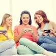 Smiling teenage girls with smartphones at home — Stock Photo #56176087