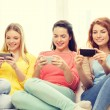 Smiling teenage girls with smartphones at home — Stock Photo #56176233
