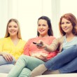 Three smiling teenage girl watching tv at home — Stock Photo #56177377
