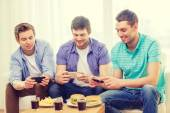 Smiling friends taking picture of food at home — Stock Photo