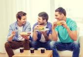 Smiling friends with soda and hamburgers at home — Stock Photo