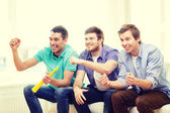 Happy male friends with vuvuzela watching sports — Stock Photo