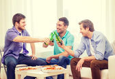 Smiling friends with beer and pizza hanging out — Stock Photo