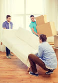 Smiling friends with sofa and boxes at new home — Stock Photo