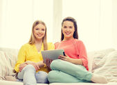 Two smiling teenage girls with tablet pc at home — Stock Photo