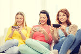 Smiling teenage girls with smartphones at home — Stock Photo