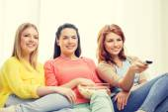 Three smiling teenage girl watching tv at home — Stock Photo