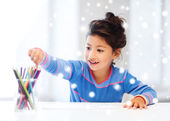 Smiling little girl with pencils drawing at home — Stock Photo