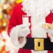 Santa claus with glass of milk and cookies — Stock Photo #56185995