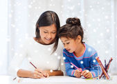 Mother and daughter with coloring pencils indoors — Stock Photo