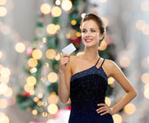 улыбающаяся женщина в вечернем наряде, держащем кредитную карту — Стоковое фото